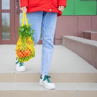 Gele string tas met komkommers, tomaten, bananen en kruiden in handen van meisje in spijkerbroek, rode jas. heldere foto in rode, gele en groene tinten. duurzaamheid, afvalvrij, plasticvrij concept.