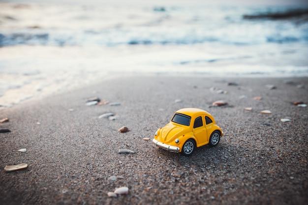 Gele stuk speelgoed auto op het strand in het zonlicht in de zomer.