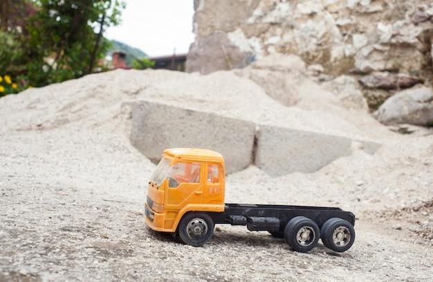 Gele stuk speelgoed vrachtwagen op het zand