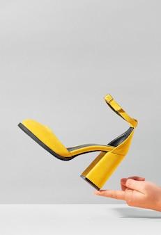 Gele suède schoen met hoge hakken balanceren op de vinger van de vrouwelijke hand.