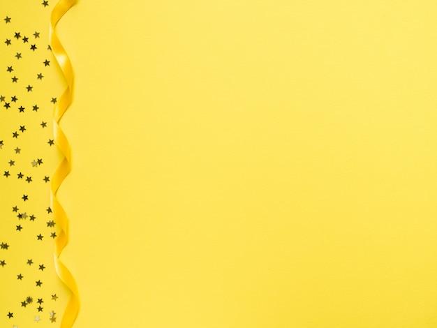 Gele tape langs de gele achtergrond. confetti-ster inlijsten
