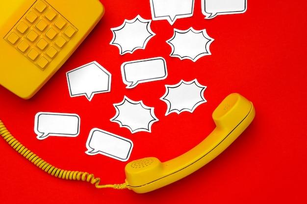 Gele telefoonspreker en tekstballon op rood oppervlak