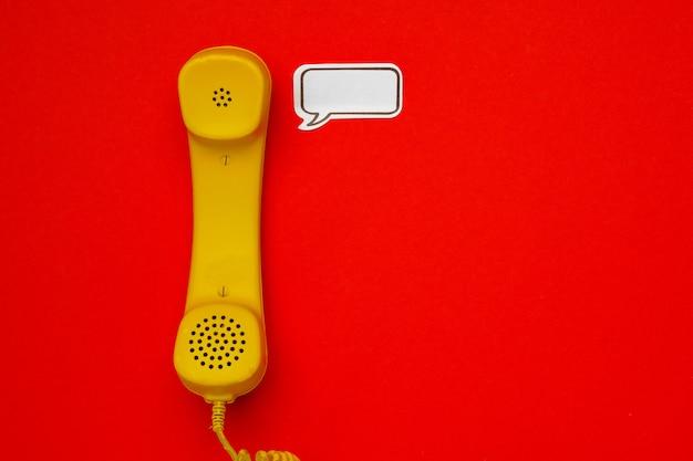 Gele telefoonspreker en toespraakbel op rode achtergrond