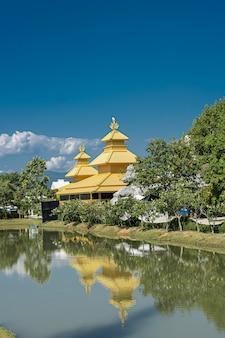 Gele tempel die in het meer in noordelijk thailand wordt weerspiegeld