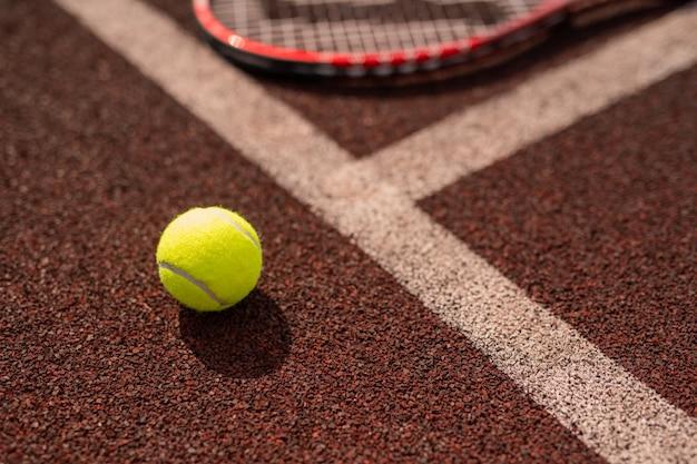 Gele tennisbal door witte lijn van sportenspeeltuin en zijn schaduw