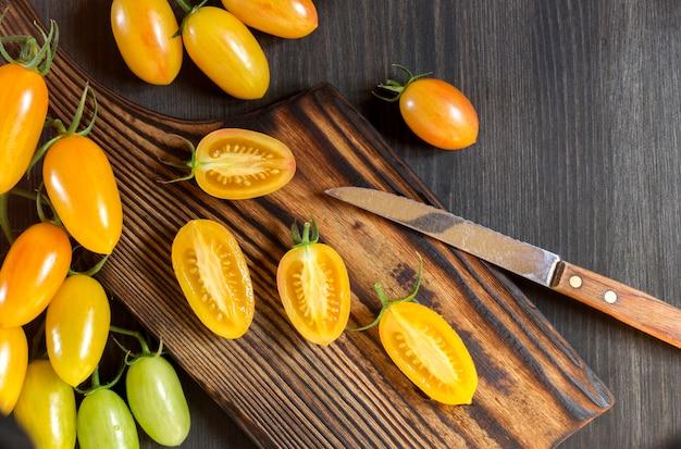 Gele tomaten op een houten bord.