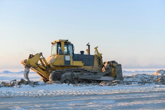 Gele tractor in de wintertoendra. de wegenbouw. bulldozer.