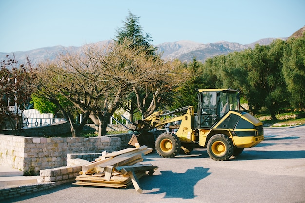 Gele tractor met een emmer staat op de weg