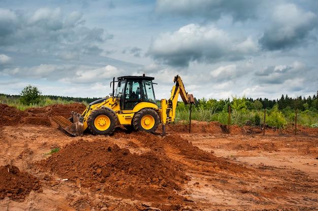 Gele tractor op een bouwplaats zet de polen in het veld