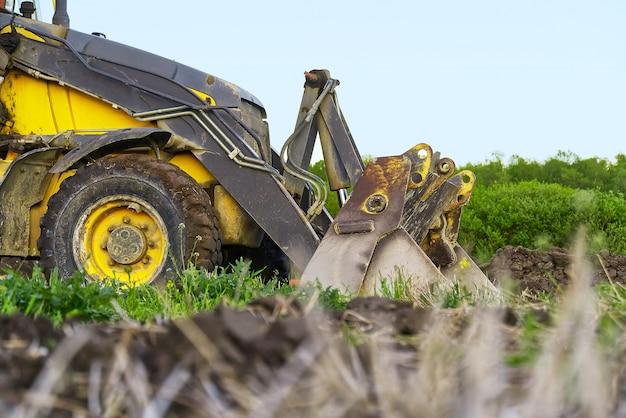 Gele tractor op het zijdelings onder ogen gezien gebied.
