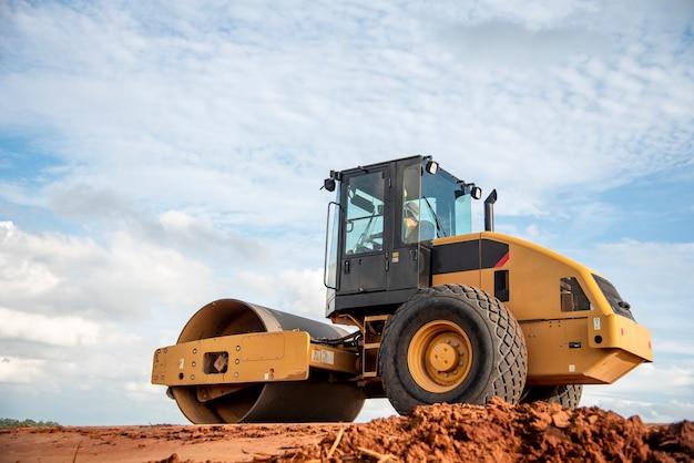 Gele trillingsgrondverdichter die aan wegbouwwerf werken