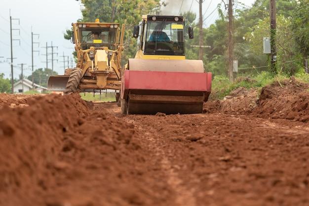 Gele trillingsgrondverdichter die aan wegbouwwerf werken.