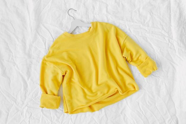 Gele trui. herfst kleding op witte achtergrond. bovenaanzicht plat lag.
