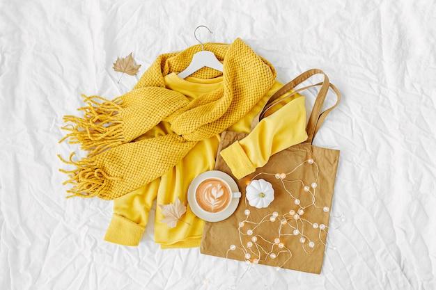 Gele trui met gebreide sjaal, draagtas en cacaodrank. herfst stemming. mode kleding collage op witte achtergrond. bovenaanzicht plat lag.