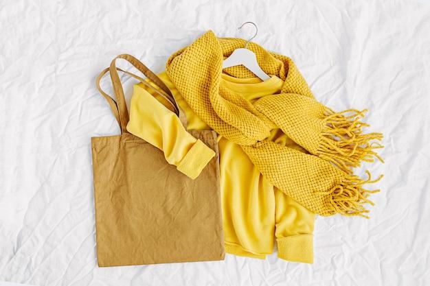 Gele trui met gebreide sjaal en draagtas. herfst mode kleding collage op witte achtergrond. bovenaanzicht plat lag.