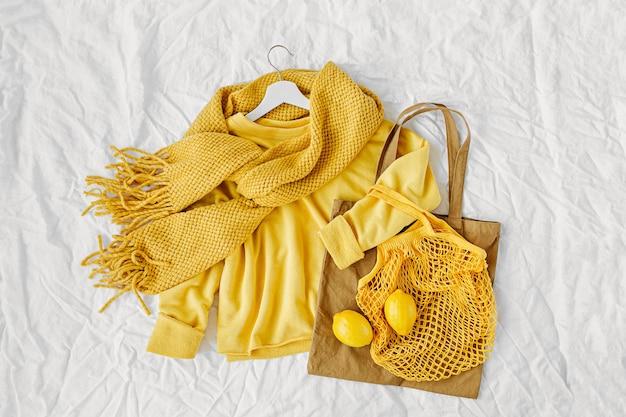 Gele trui met gebreide sjaal en eco tassen. herfst stemming. mode kleding collage op witte achtergrond. bovenaanzicht plat lag.