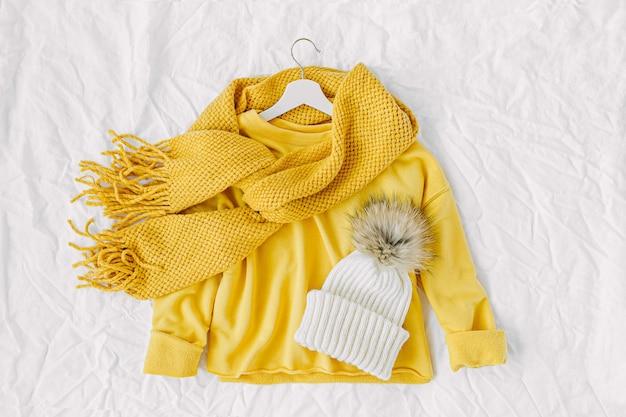 Gele trui met gebreide sjaal en muts. herfst mode kleding collage op witte achtergrond. bovenaanzicht plat lag.