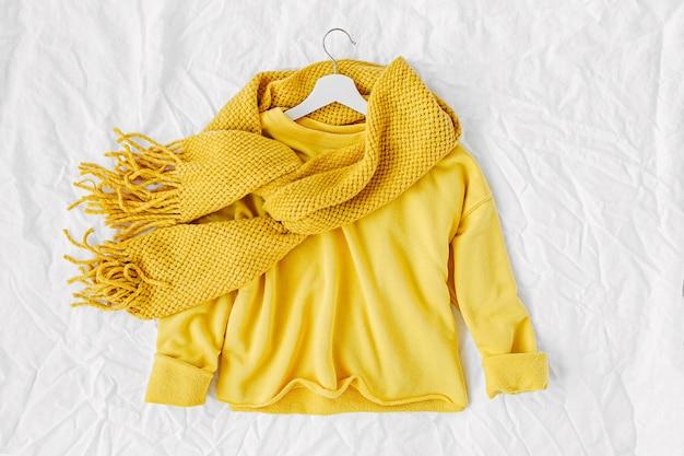 Gele trui met gebreide sjaal. herfst mode kleding collage op witte achtergrond. bovenaanzicht plat lag.