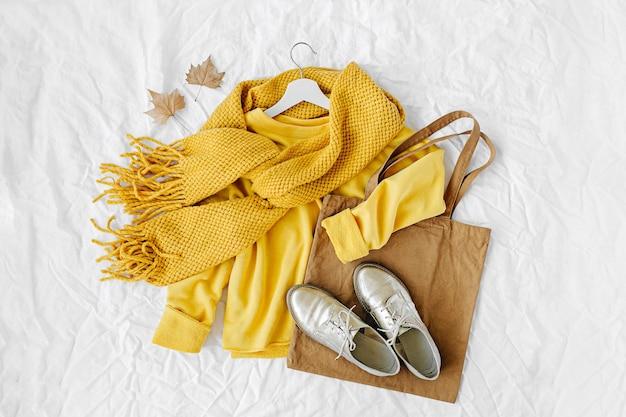 Gele trui met gebreide sjaal, schoenen en draagtas. herfst mode kleding collage op witte achtergrond. bovenaanzicht plat lag.