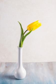Gele tulp in vaas op tafel