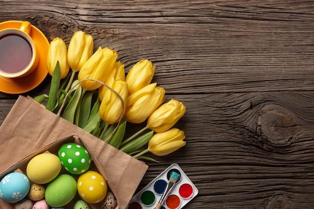Gele tulpen, een nest met paaseieren, heldere kleuren en een palet op een houten achtergrond. bovenaanzicht met kopie ruimte.