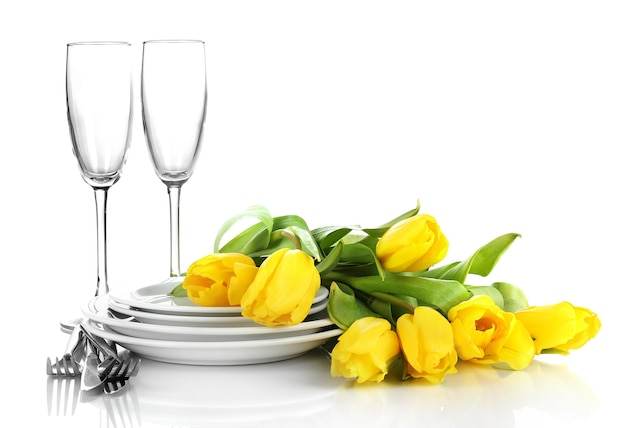 Gele tulpen en keukengerei voor het serveren op wit wordt geïsoleerd