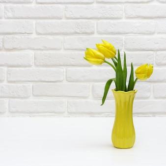 Gele tulpen in vaas. heldere bloeiende lentebloemen op witte decoratieve bakstenen muur.