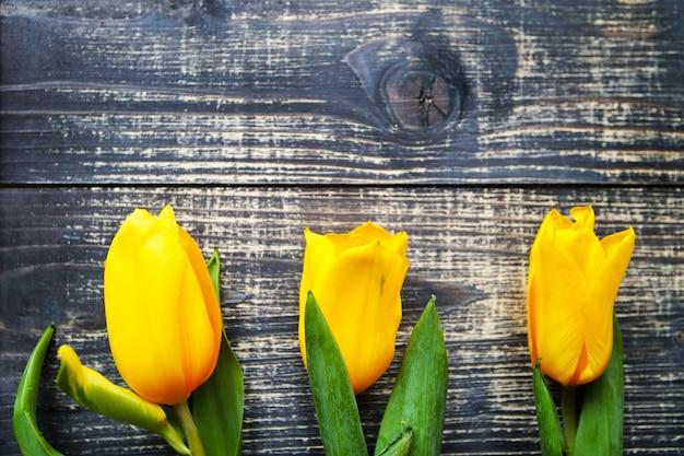 Gele tulpen liggen op een zwarte oude vintage houten tafel achtergrond.