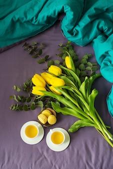 Gele tulpen, macarons en twee kopjes thee in bed