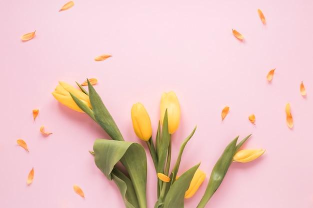 Gele tulpen met bloemblaadjes op tafel