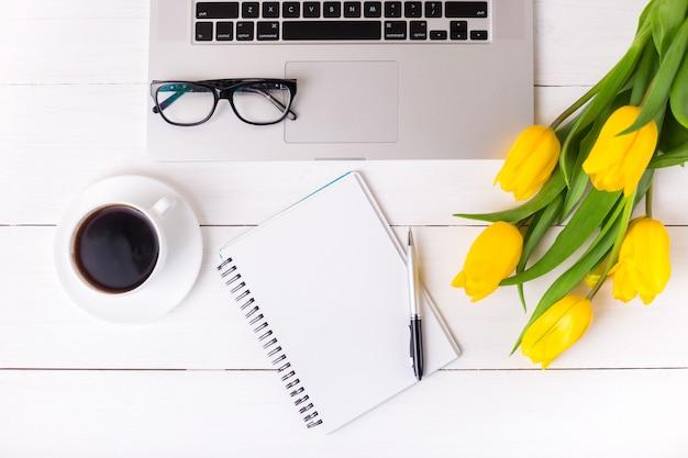 Gele tulpen met een feestelijke sfeer en koffie op witte houten planken. notebook en bril.