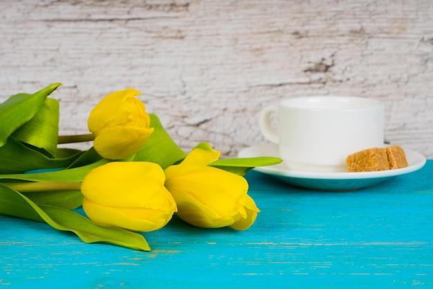 Gele tulpen met een koffiekopje op turquoise houten tafel