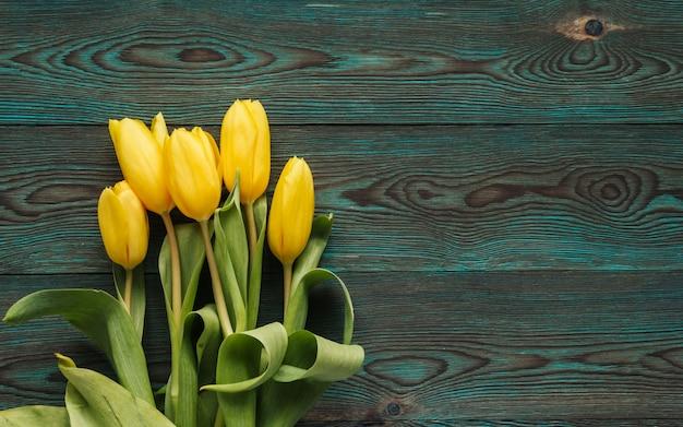 Gele tulpen op een blauwe houten achtergrondexemplaarruimte. boeket van gele tulpen plat lag.