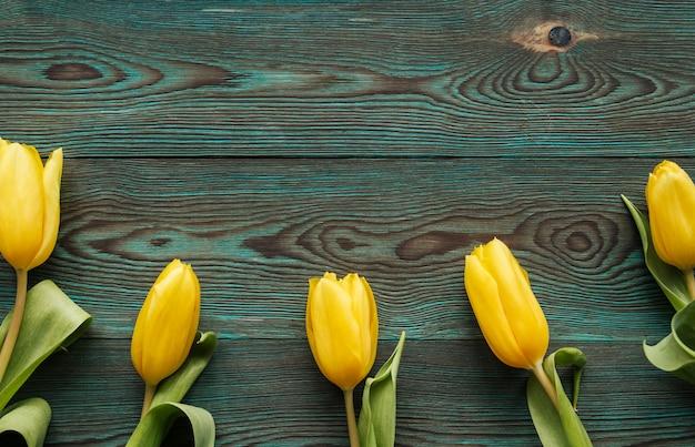 Gele tulpen op een blauwe houten achtergrondexemplaarruimte. tulp plat lag