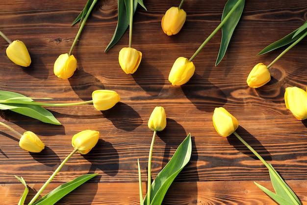 Gele tulpen op een bruine houten achtergrond op een zonnige lentedag.