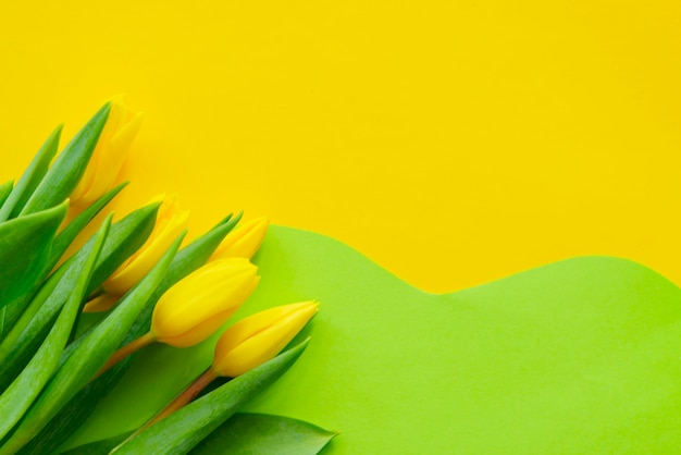 Gele tulpen op een geometrische geel-groene achtergrond, wenskaart voor vrolijk pasen, kopie ruimte
