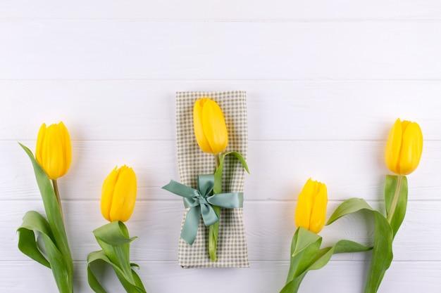 Gele tulpen op een servet gebonden met een strik. achtergrond voor menu. plat leggen, ruimte kopiëren
