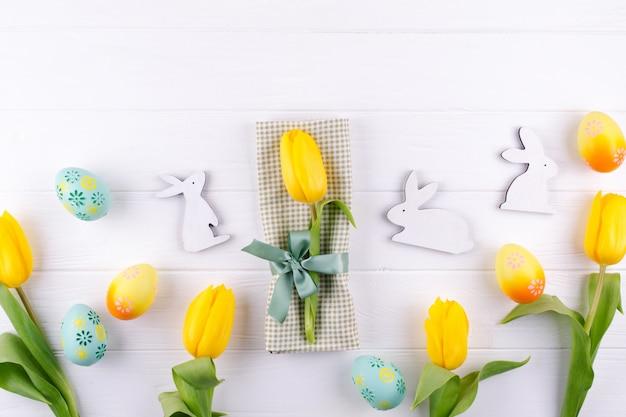 Gele tulpen op een servet vastgebonden met een strik op witte houten tafel. achtergrond voor menu. plat leggen, ruimte kopiëren