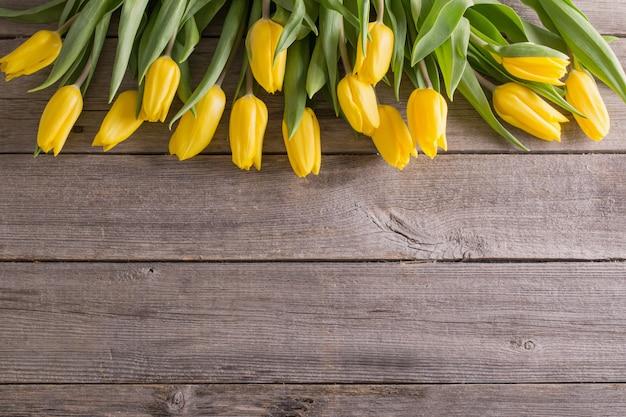 Gele tulpen op houten tafel achtergrond