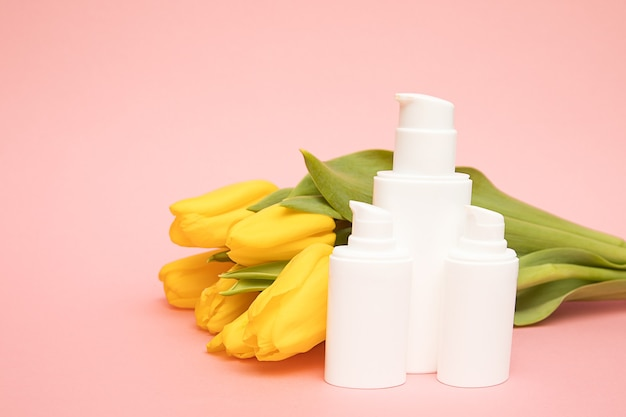 Gele tulpen op roze achtergrond met cosmetische flessen containers. bespotten. gelukkige moederdag, vrouwendag gefeliciteerd concept, geschenk, koreaanse cosmetica met bloemen