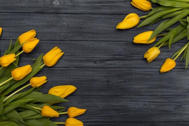 Gele tulpen op vintag houten achtergrond. de lenteachtergrond met tulpen, exemplaarruimte voor tekst. plat lag, bovenaanzicht.