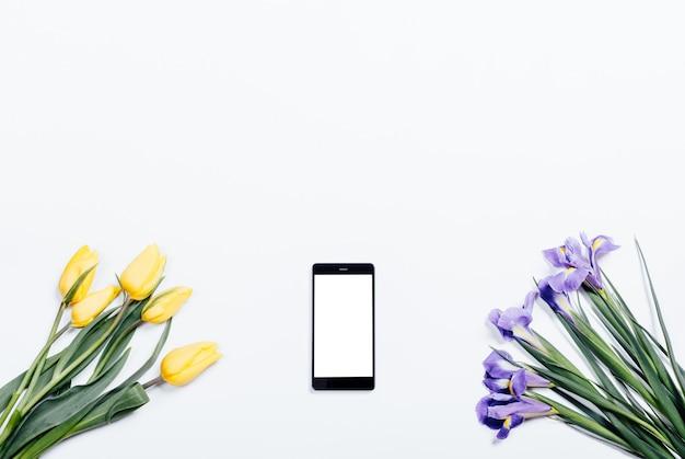 Gele tulpen, paarse irissen en mobiele telefoon op een witte achtergrond