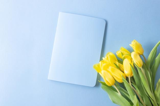 Gele tulpenbloemen op blauwe achtergrond met een open notitieblok om te schrijven. moederdag, verjaardag, valentijnsdag. concept van vakantie. symbool van de lente. platliggend, bovenaanzicht, kopieerruimte