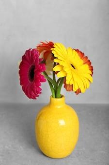 Gele vaas met boeket van mooie gerbera's op grijze achtergrond