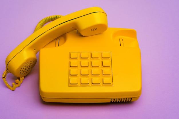 Gele vaste telefoon op paars oppervlak close-up