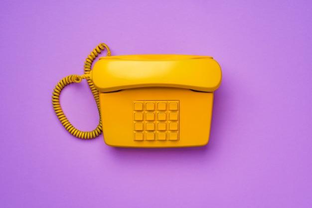 Gele vaste telefoon op paarse close-up