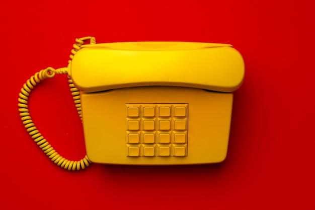 Gele vaste telefoon op rode bovenaanzicht