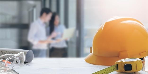 Gele veiligheidshoed en techniekhulpmiddelen op de lijst met de achtergrond van het onduidelijk beeldbeeld van de vergadering van het ingenieursteam.