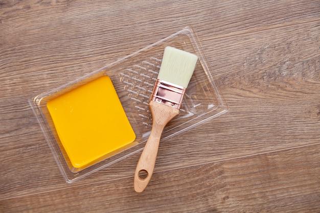 Gele verf op houten bruine vloer, borstel