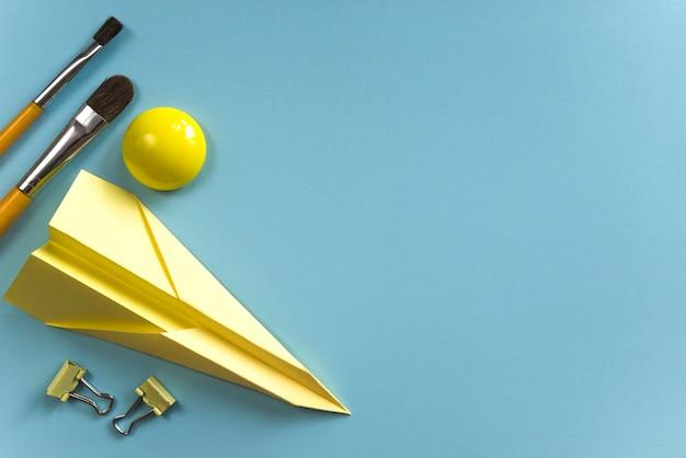 Gele verfborstels en papieren vliegtuig voor inspiratie